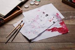 Μια άποψη των αντικειμένων για το σχέδιο Βούρτσες, χρώματα σε ένα κιβώτιο για τα υλικά στο ξύλινο παρκέ τέχνης ανασκόπησης μαύρο  Στοκ Φωτογραφίες