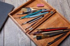 Μια άποψη των αντικειμένων για το σχέδιο Βούρτσες, χρώματα σε ένα κιβώτιο για τα υλικά στο ξύλινο παρκέ τέχνης ανασκόπησης μαύρο  Στοκ φωτογραφία με δικαίωμα ελεύθερης χρήσης