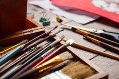 Μια άποψη των αντικειμένων για το σχέδιο Βούρτσες, χρώματα σε ένα κιβώτιο για τα υλικά στο ξύλινο παρκέ τέχνης ανασκόπησης μαύρο  Στοκ Εικόνες