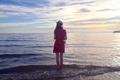 Μια άποψη των κοριτσιών πίσω στην παραλία και τον ουρανό ηλιοβασιλέματος Στοκ εικόνες με δικαίωμα ελεύθερης χρήσης