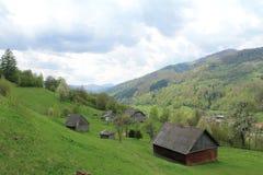 Μια άποψη των πράσινων Καρπάθιων λόφων με τα ξύλινα σπίτια στοκ εικόνες