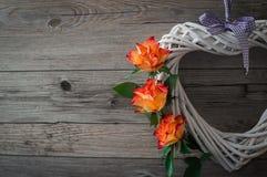 Μια άσπρη καρδιά φιαγμένη από άμπελο Όμορφα πορτοκαλιά τριαντάφυλλα στο ανοικτό γκρι ξύλινο υπόβαθρο Στοκ Εικόνες