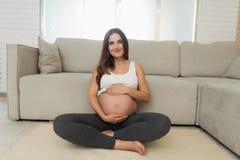 Μια έγκυος γυναίκα κάθεται σε ένα ελαφρύ πάτωμα στο σπίτι Κάθεται cross-legged στο πάτωμα και προσκολλάται στην κοιλιά της Στοκ Εικόνα