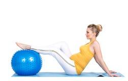 Μια έγκυος γυναίκα κάνει τη γυμναστική με τη σφαίρα Στοκ Εικόνα