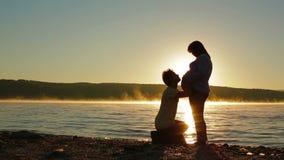 Μια έγκυος γυναίκα και ένας αναμένων πατέρας στη σκιαγραφία λιμνών φιλμ μικρού μήκους