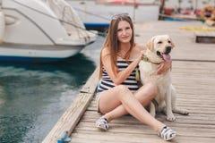 Μια έγκυος γυναίκα με ένα σκυλί στην αποβάθρα Στοκ Φωτογραφίες