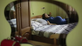 Μια έγκυος νέα γυναίκα σε ένα μπλε φόρεμα βρίσκεται στο κρεβάτι και καθίσταται άνετος απόθεμα βίντεο