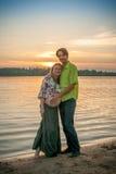 Μια έγκυος όμορφη γυναίκα με το σύζυγό της στην παραλία όχθεων ποταμού που χαμογελά και σχετικά με την κοιλιά της με την αγάπη κα Στοκ Εικόνες