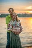 Μια έγκυος όμορφη γυναίκα με το σύζυγό της στην παραλία όχθεων ποταμού που χαμογελά και σχετικά με την κοιλιά της με την αγάπη κα Στοκ Φωτογραφία