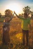 Μια έγκυος όμορφη γυναίκα με το σύζυγό της στο τοπίο φύσης που χαμογελά και σχετικά με την κοιλιά της με την αγάπη και την προσοχ Στοκ Εικόνα