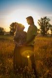 Μια έγκυος όμορφη γυναίκα με το σύζυγό της στο τοπίο φύσης που χαμογελά και σχετικά με την κοιλιά της με την αγάπη και την προσοχ Στοκ φωτογραφίες με δικαίωμα ελεύθερης χρήσης