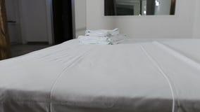 Μια έξοδος είναι δίπλα στο διπλό κρεβάτι σε ένα δωμάτιο ξενοδοχείου με με έναν καθρέφτη στον τοίχο απόθεμα βίντεο