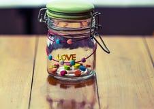 Μια ΑΓΑΠΗ λέξης και μια καρδιά-μορφή της καραμέλας ζελατίνας σε ένα βάζο γυαλιού επιζητούν επάνω στοκ φωτογραφίες