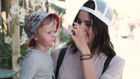 Μια αγαπώντας μητέρα ταΐζει το παιδί της με ένα παγωτό Ένα μικρό αγόρι τρώει ευτυχώς, έχοντας τα πνεύματά του υψηλά και αντιμετωπ φιλμ μικρού μήκους