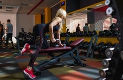 Μια αθλήτρια συμμετέχει σε μια γυμναστική με τους αλτήρες μετάλλων στον πάγκο για τον Τύπο πάγκων Στοκ Εικόνα