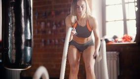 Μια αθλητική γυναίκα στην κατάρτιση στη γυμναστική Κατάρτιση των χεριών της με το χτύπημα σχοινιών φιλμ μικρού μήκους