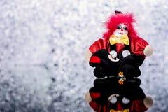 Μια ανατριχιαστική κούκλα κλόουν στο ασημένιο λαμπρό υπόβαθρο Στοκ φωτογραφία με δικαίωμα ελεύθερης χρήσης