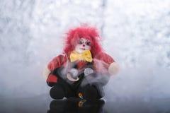 Μια ανατριχιαστική κούκλα κλόουν στο ασημένιο λαμπρό υπόβαθρο Στοκ Εικόνες