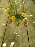 Μια ανθοδέσμη της φράουλας και των άγριων λουλουδιών και χορτάρια σε ένα γυαλί/γυαλί γυαλί σε έναν μακρύ δρύινο πίνακα στοκ εικόνα με δικαίωμα ελεύθερης χρήσης
