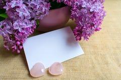 Μια ανθοδέσμη των ιωδών λουλουδιών σε ένα ιώδες βάζο και έναν φάκελο Κάρτα r στοκ εικόνα