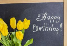 """Μια ανθοδέσμη των κίτρινων τουλιπών και η επιγραφή στην κιμωλία """"χρόνια πολλά """" στοκ εικόνα"""