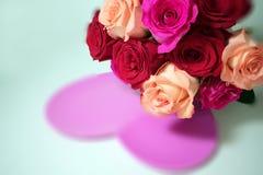 Μια ανθοδέσμη των κόκκινων και ρόδινων τριαντάφυλλων πέρα από τη ρόδινη καρδιά στοκ εικόνες