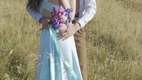 Μια ανθοδέσμη των λουλουδιών στα χέρια ενός μοντέρνου ζεύγους μια ηλιόλουστη ημέρα φιλμ μικρού μήκους