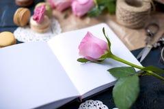 Μια ανθοδέσμη των τριαντάφυλλων είναι ρόδινη, στο γκρίζο έγγραφο και μια άσπρη καρδιά Αυξήθηκε σε ένα ανοικτό σημειωματάριο Γλυκά στοκ φωτογραφία με δικαίωμα ελεύθερης χρήσης