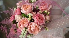 Μια ανθοδέσμη των τριαντάφυλλων και του κοράλλι-χρωματισμένου κοσμήματος στα χέρια της νύφης απόθεμα βίντεο