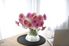 Μια ανθοδέσμη των φρέσκων λουλουδιών σε ένα βάζο στον πίνακα designed home interior living retro room style Ένας υπολογιστής Στοκ εικόνα με δικαίωμα ελεύθερης χρήσης