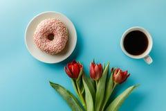 Μια ανθοδέσμη των όμορφων φρέσκων τουλιπών σε ένα μπλε υπόβαθρο και των κέικ με ένα φλιτζάνι του καφέ στοκ φωτογραφίες με δικαίωμα ελεύθερης χρήσης