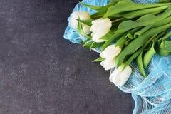 Μια ανθοδέσμη των άσπρων φρέσκων τουλιπών σε ένα μπλε αφηρημένο υπόβαθρο σύστασης Έννοια αγάπης και γάμου ρωμανικός στοκ φωτογραφία με δικαίωμα ελεύθερης χρήσης