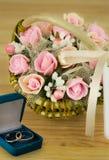 Μια ανθοδέσμη των λουλουδιών σε ένα καλάθι των χειροποίητων γαμήλιων δαχτυλιδιών Στοκ φωτογραφία με δικαίωμα ελεύθερης χρήσης