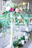 Μια ανθοδέσμη των λουλουδιών σε μια στάση με τα κεριά και το ντεκόρ για την επιτραπέζια διακόσμηση στους γάμους και τους εορτασμο Στοκ Εικόνες