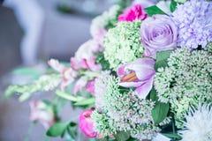 Μια ανθοδέσμη των λουλουδιών σε μια στάση με τα κεριά και το ντεκόρ για την επιτραπέζια διακόσμηση στους γάμους και τους εορτασμο Στοκ Φωτογραφία