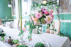 Μια ανθοδέσμη των λουλουδιών σε μια στάση με τα κεριά και το ντεκόρ για την επιτραπέζια διακόσμηση στους γάμους και τους εορτασμο Στοκ φωτογραφίες με δικαίωμα ελεύθερης χρήσης