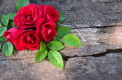 Μια ανθοδέσμη των τριαντάφυλλων στο ξύλινο παλαιό υπόβαθρο στην αριστερή γωνία στοκ φωτογραφία με δικαίωμα ελεύθερης χρήσης