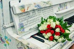 Μια ανθοδέσμη των τριαντάφυλλων στο πιάνο Στοκ Εικόνες