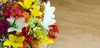 Μια ανθοδέσμη των φωτεινών μεγάλων λουλουδιών σε ένα ξύλινο υπόβαθρο διάστημα αντιγράφων Ρομαντική διάθεση Κάρτα λουλουδιών με τη Στοκ Εικόνες