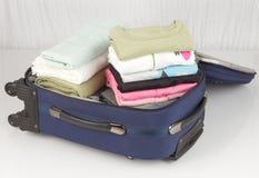 Ανοιγμένη βαλίτσα που συσκευάζεται με πολλά ζωηρόχρωμα υφάσματα Στοκ εικόνα με δικαίωμα ελεύθερης χρήσης