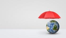 Μια ανοικτή κόκκινη ομπρέλα που στέκεται κάθετα στη λαβή και που κρατά ασφαλή μια μικρή γήινη σφαίρα Στοκ Εικόνες