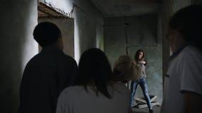 Μια αποκάλυψη zombie Επιζημένη γυναίκα με ένα πυροβόλο όπλο που περπατά έξω από τον τοίχο και που στοχεύει στα zombies απόθεμα βίντεο