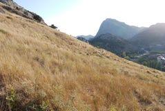 Μια απότομη κάθοδος ενάντια στο σκηνικό μιας σειράς βουνών και μιας μικρής λίμνης στοκ εικόνες
