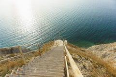 Μια απότομη κάθοδος κάτω από τα μακριά σκαλοπάτια μετάλλων στην ακτή της μπλε θάλασσας στοκ εικόνες