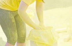 Μια από την επίσημη γυναίκα που συλλέγει την κίτρινη σκόνη χρώματος Στοκ εικόνα με δικαίωμα ελεύθερης χρήσης
