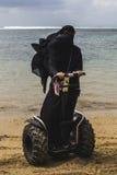 Μια αραβική γυναίκα οδηγά έναν segway σε μια παραλία Στοκ Φωτογραφίες