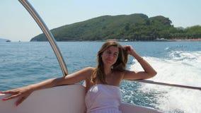Μια αρκετά νέα καυκάσια γυναίκα στην άσπρη συνεδρίαση φορεμάτων σε μια επιπλέουσα βάρκα εν πλω απόθεμα βίντεο