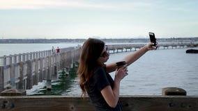 Μια αρκετά νέα χιλιετής λήψη γυναικών brunette selfies σε έναν ωκεάνιο θαλάσσιο περίπατο με τα αποτελέσματα της φιλμ μικρού μήκους