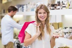 Μια αρκετά ξανθή γυναίκα που εξετάζει το προϊόν ομορφιάς Στοκ Εικόνες