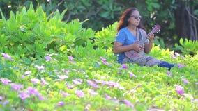 Μια ασιατική γυναίκα με τα sunglass που παίζουν ukulele απόθεμα βίντεο